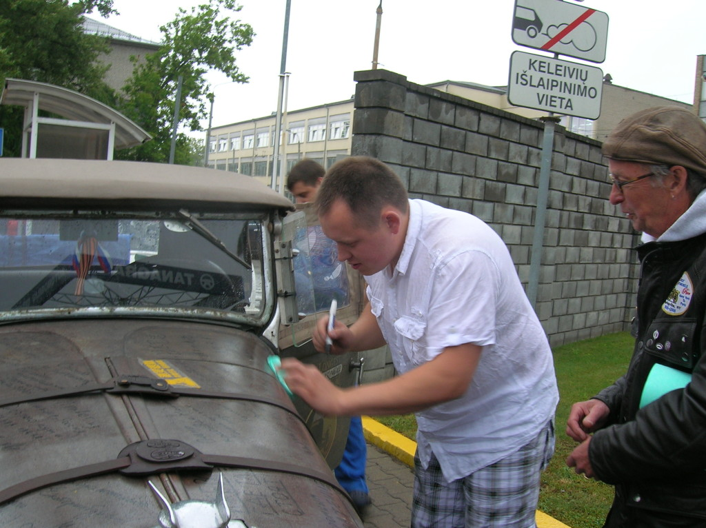 Augustus Jansonns, the salesman who helped us, signs the car